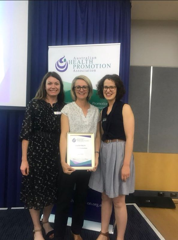 Fiona Phillips on stage at the Australian Health Promotion Association WA awards accepting her award alongside Kelly Kennington and Lorena Chapman